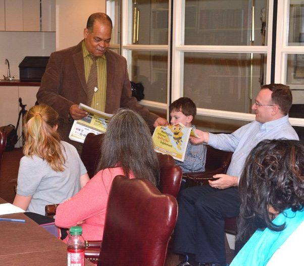 Ron Burke Director of Advertising and Marketing for the Washington Informer distributes the spelling bee supplement to the winners and their parents Thursday, April 14.