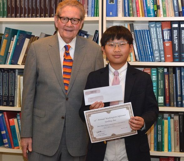 Attorney Jack Olender presents First place winner of the 34th Annual Washington Informer Spelling Bee, William Cho with the grand prize of $1000 and a certificate April 14.