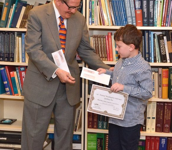 Attorney Jack Olender presents Third place winner of the 34th Annual Washington Informer Spelling Bee, Harrison Hackett with the 3rd place prize of $300 and a certificate April 14.
