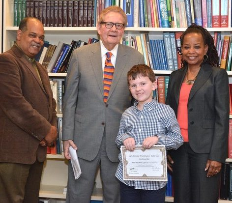 Third place winner of the 34th Annual Washington Informer Spelling Bee, Harrison Hackett poses for a group photo with Attorney Jack Olender, publisher of The Washington Informer Denise Rolark Barnes and Director of advertising Ron Burke Thursday, April 14,