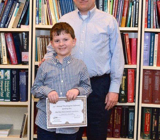 Third place winner of the 34th Annual Washington Informer Spelling Bee, Harrison Hackett poses for a photo with his father upon receiving his cash prize and certificate Thursday, April 14.
