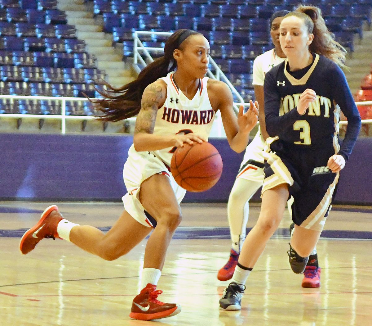 Howard Lady Bison guard Te'Shya Heslip drives past Mount St. Mary's Mountaineers guard Kathleen Belanger-Finn in the first quarter of Howard's 95-62 win at Burr Gymnasium in Northwest on Saturday, Dec. 10. /Photo by John E. De Freitas