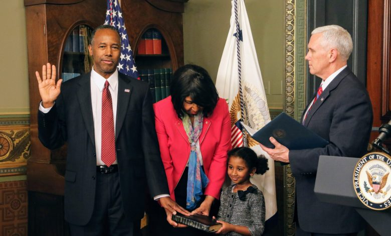 Ben Carson (left) is sworn in by Vice President Mike Pence as the Trump administration's secretary of Housing and Urban Development in the Eisenhower Executive Office Building on the White House complex on March 3, as his wife Candy and 5-year-old granddaughter, Tesora, hold the Bible. (Shevry Lassiter/The Washington Informer)