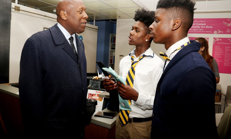 Keidez Thompson (right) and Gabriel Davis (center), both 10th-grade students at Friendship Collegiate Academy Public Charter School in Northeast, deliver a sales pitch of their Bliss Bag Straps to Fred Griffin, a senior sales executive at Prime Pay, during the Spring Sales Bazaar hosted by BUILD Metro DC at the Pepco Gallery in Northwest. (Shevry Lassiter/The Washington Informer)