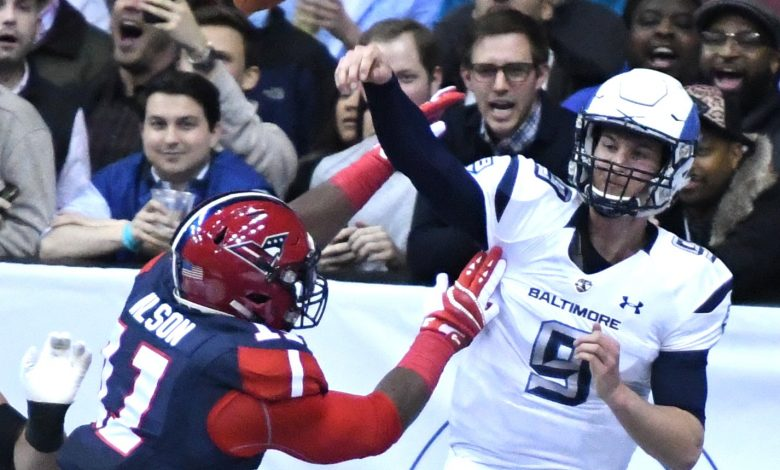 Baltimore Brigade quarterback Shane Carden (9) attempts a pass as Washington Valor defensive lineman Reggie Wilson closes in during the first quarter of the Valor's 51-38 win at Verizon Center in D.C. on April 7. (John E. De Freitas/The Washington Informer)