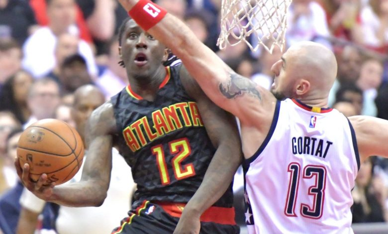 Atlanta Hawks forward Taurean Prince (12) attempts a shot around Washington Wizards center Marcin Gortat in the first quarter of the Wizards' 114-107 win in Game 1 of the Eastern Conference first-round playoff series at Verizon Center in D.C. on April 16. (John De Freitas/The Washington Informer)