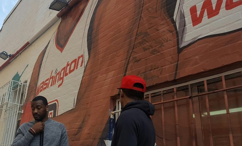 Washington Wizards guards John Wall (left) and Bradley Beal stand in front a mural depicting the two outside Ben's Chili Bowl in northwest D.C. on April 13. (William J. Ford/The Washington Informer)