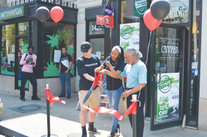 The History of Cannabis Museum staff celebrates the opening with a ribbon cutting on April 20 in Northwest. (Photo by Steve Garrett)