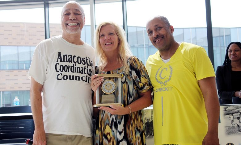 """Phil Pannell, of the Anacostia Coordinating Council, and Ron Moten, of the Jack Kemp Foundation, present a clock to former MPD Assistant Chief Diane Grooms for her """"compassionate"""" service to residents, particularly in Wards 7 and 8. (Courtesy photo)"""