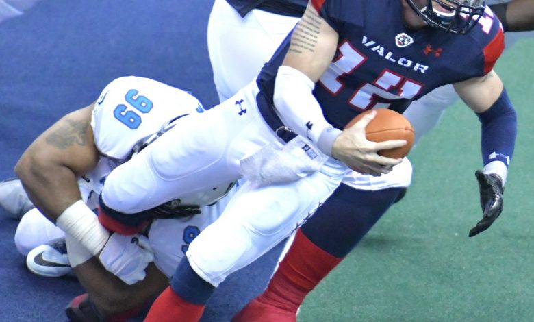 Washington Valor quarterback Sean Brackett is tackled by Philadelphia Soul defensive lineman Justin Lawrence during Philadelphia's 48-47 win at Verizon Center in D.C. on May 27. (John E. De Freitas/The Washington Informer)
