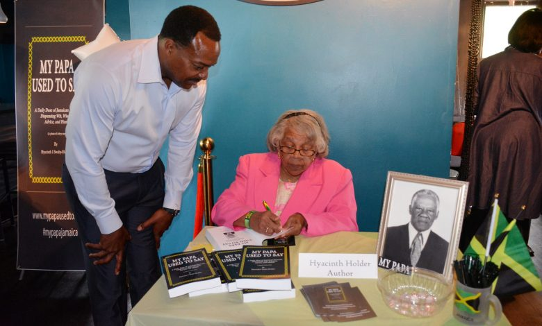 "Leon Harris, NBC4 anchor, gets his book signed by Hyacinth Holder, author of ""My Papa Used to Say,"" at the Jerk Pit in College Park, Md., on May 27. (Roy Lewis/The Washington Informer)"