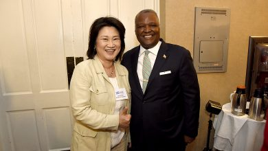 Prince George's County Executive Rushern L. Baker III (right) poses with Theresa Nam, president of KL USA of College Park, during Baker's State of the Economy address at the Colony South Hotel and Conference Center in Clinton on May 3. Nam established a small business in October that manufactures capacitors in College Park. (Mike Yourishin/County Executive's Office)