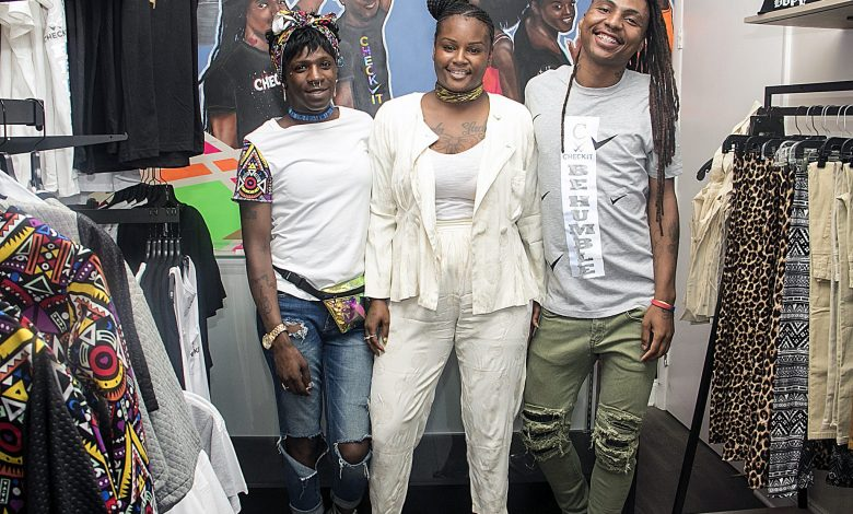 "From left: Star Bennett, 27 of Northeast, Erica ""Eboll"" Briscoe, 26 of Northeast and Michael Boatwright, 27 of Southeast, co-founders of Check It, pause for a photo op during the grand opening of their new store in Anacostia. (Shevry Lassiter/The Washington Informer)"