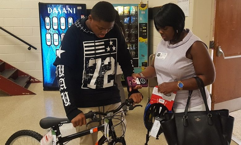 Daniel Pearson (left), a seventh-grader at Dwight D. Eisenhower Middle School in Laurel, Maryland, and his mother, Josephine Dallas, look at one of the new bicycles and helmets given by a local auto dealership during a June 8 school assembly as rewards to Pearson and fellow classmates for maintaining perfect attendance throughout the 2016-17 school year. (William J. Ford/The Washington Informer)