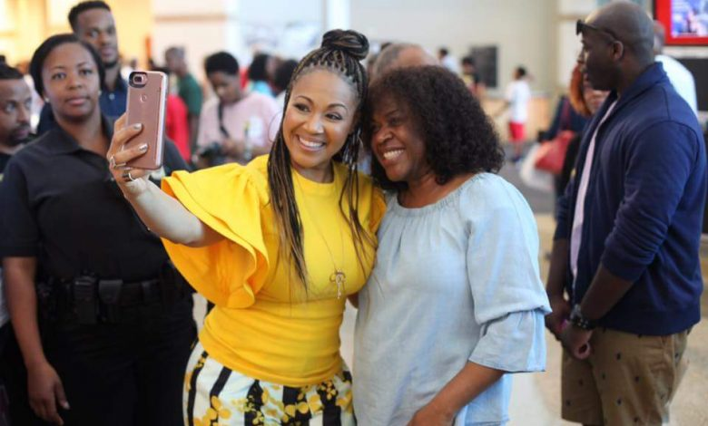 Gospel recording artist Erica Campbell (in yellow) takes a photo with Lady Trina Jenkins at the First Baptist Church of Glenarden's annual Health and Wellness Expo in Upper Marlboro, Maryland, on June 10. (Courtesy of First Baptist Church via Facebook)