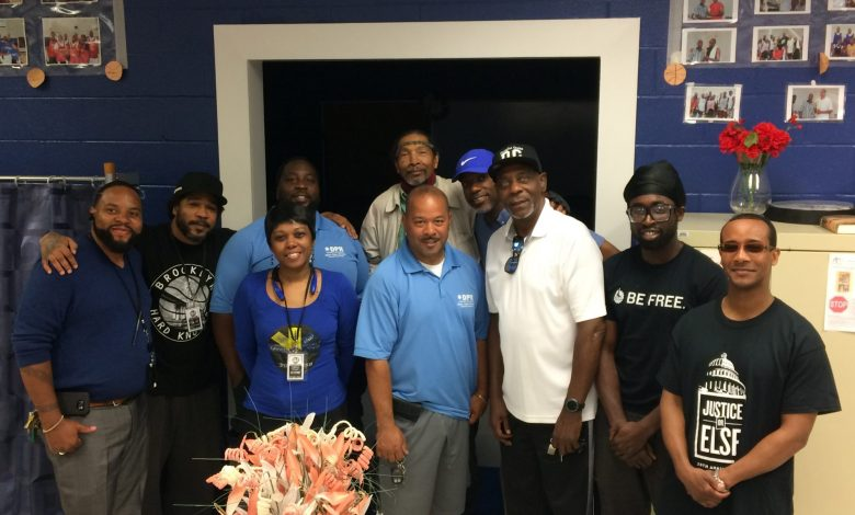Craig Hughes (light blue shirt in the center), DPR recreation specialist at Emery Heights Recreation Center, poses with members of the Man Cave planning committee after one of their meetings. (Courtesy of Krystal Branton)