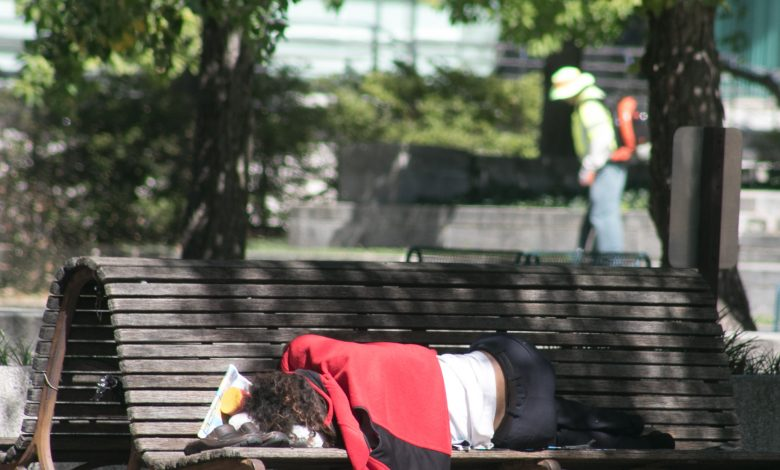 A homeless woman sleeps on a bench in front of the Canadian Embassy. (Shevry Lassiter/The Washington Informer)