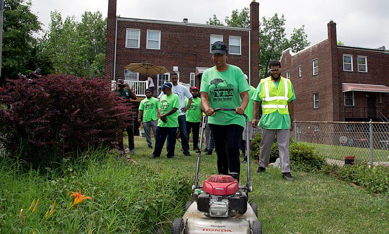 D.C. Mayor Muriel E. Bowser helps mow 81-year-old District resident Evelyn Young's yard as part of a lawn maintenance project for city seniors. (Lateef Mangum/The Washington Informer)