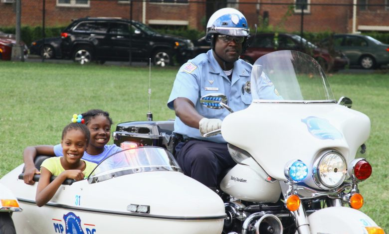 Maleyah Wilkinson, 9, and Alajha Gamble, 9, ride along in the sidecar of a MPDC motorcycle, one of the activities available during the National Night Out event at the King Greenleaf Recreation Center in D.C.'s Ward 6 on Aug. 1. (E Watson/EDI Photos)