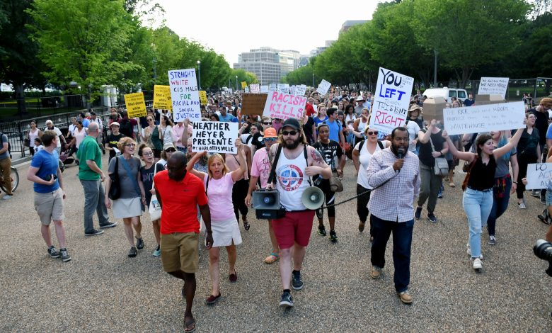 Activist Eugene Puryear (right) leads protesters past Trump Hotel to the confederate statue of Albert Pike near Metropolitan Police Department headquarters after a prayer vigil at Lafayette Park in northwest D.C. on Aug. 13. (Roy Lewis/The Washington Informer)
