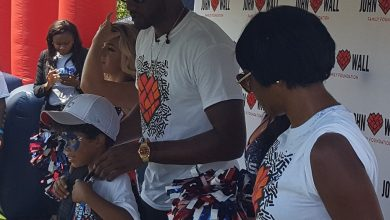 """Washington Wizards guard John Wall helps a child put on a backpack during his John Wall Family Foundation's annual """"Back to School"""" event at the Rosedale Community Center in northwest D.C. on Aug. 18. (William J. Ford/The Washington Informer)"""