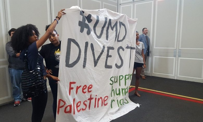 "University of Maryland students and an alumnus hold a large sign, ""#UMD Divest. Free Palestine, support human rights,"" during an Aug. 31 conversation on race, politics and reconciliation on the College Park campus. (William J. Ford/The Washington Informer)"