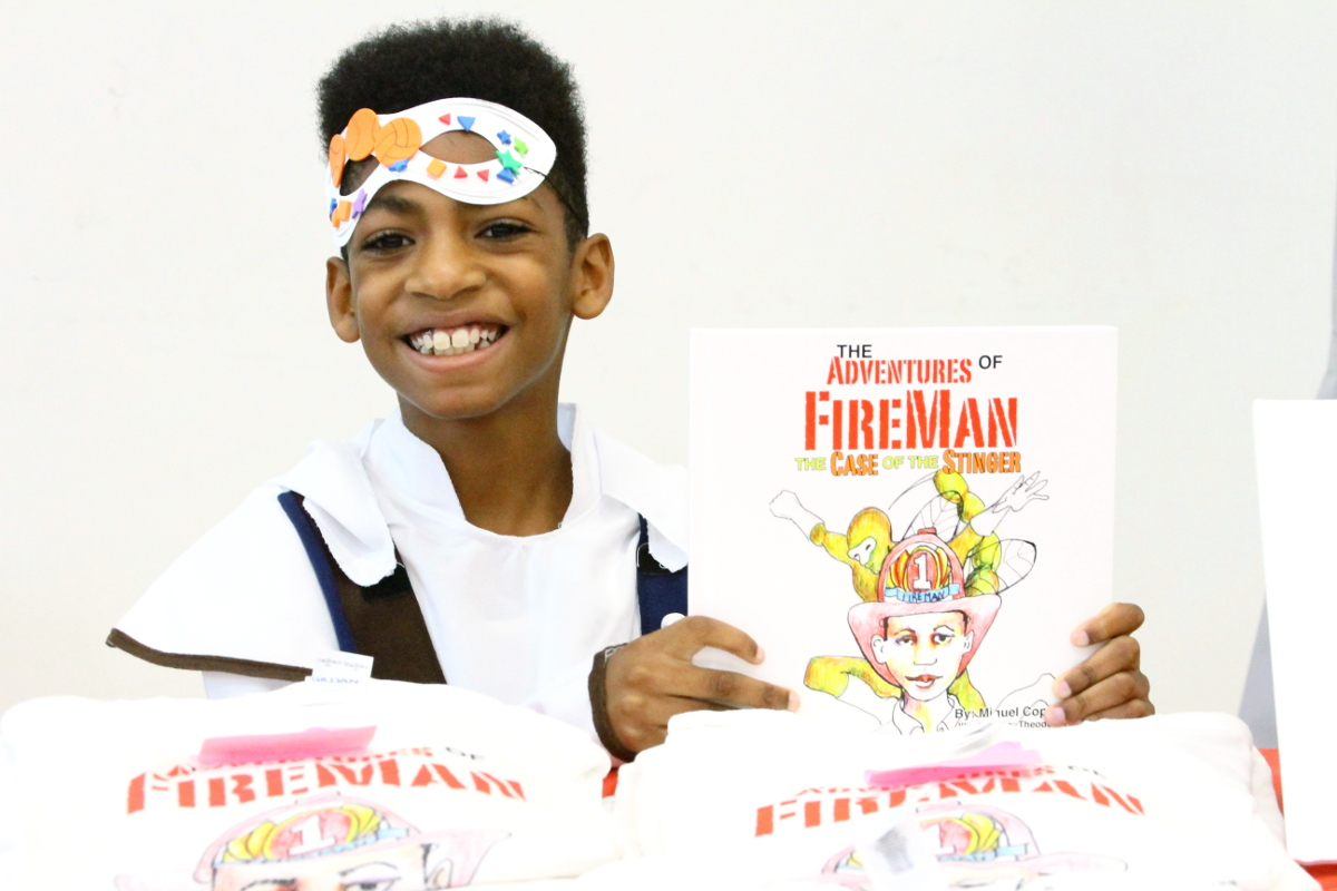 Youth author Miguel Coppedge, 11, a northeast D.C. resident offers branded T-shirts and autographed copies of his books at the 2017 East of the River Book Festival at Rise Academy in Southeast on Oct. 14. Coppedge wrote his first book at age 8 and now has four independently published books. (E Watson/EDI Photo)