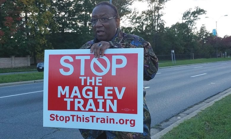William Dixson of Bowie, Maryland, holds a sign to show his disapproval of a proposed $10 billion high-speed train project known as Maglev outside an Oct. 24 open house hosted by the state Department of Transportation at Laurel High School to discuss the project. (William J. Ford/The Washington Informer)