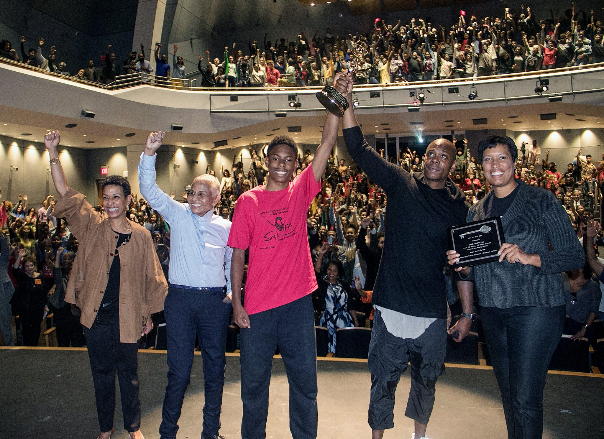 """From left: Duke Ellington School of the Arts Chief Executive Officer Tia Powel Harris, Peggy Cooper Cafritz, co-founder of the Duke Ellington School of the Arts and former president of D.C.'s school board, Ellington freshman Makeal Exum, comedian Dave Chappelle and D.C. Mayor Muriel Bowser lift hands in celebration at the Northwest school on Sept. 29, after Chappelle was presented with the Key to the City and gifted the school with an Emmy he received for an appearance on """"Saturday Night Live"""" earlier this year. (Shevry Lassiter/The Washington Informer)"""