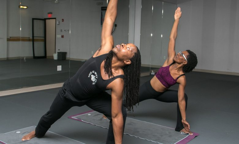 Omekongo Dibinga and Kendra Blackett-Dibinga pose in harmony at their Ivy City yoga studio. (Shevry Lassiter/The Washington Informer)
