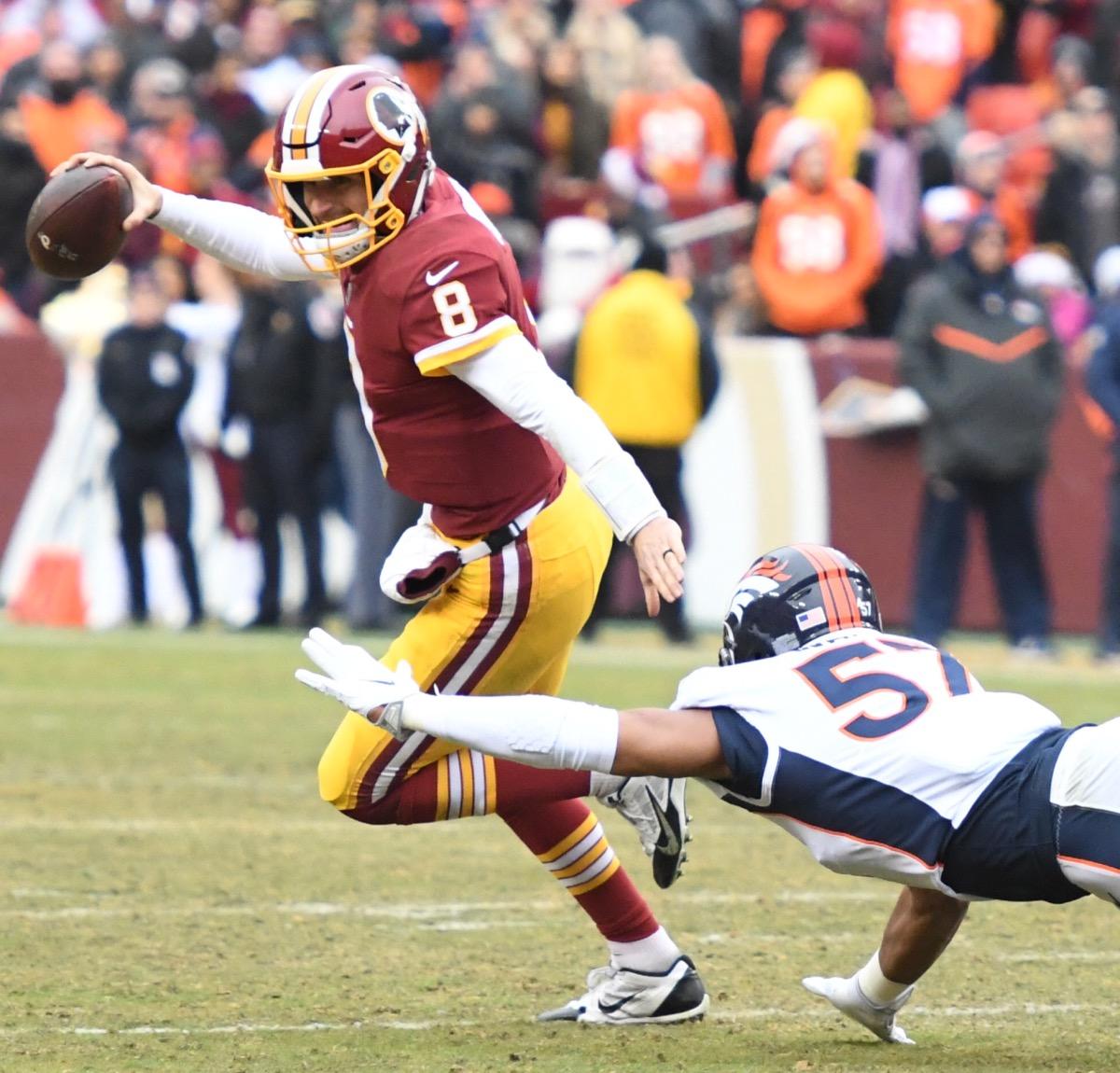 Washington Redskins quarterback Kirk Cousins slips away from Denver Broncos defensive end DeMarcus Walker during the Redskins' 27-11 win at FedEx Field in Landover, Md., on Dec. 24. (John E. De Freitas/The Washington Informer)