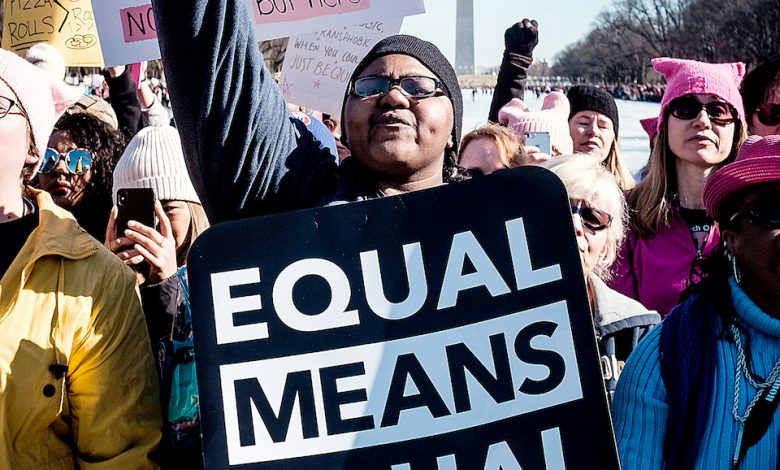 A protester holds a sign at the Lincoln Memorial to rally before the second annual Women's March in D.C. celebrating women's rights on Jan. 20, 2018. (Michael A. McCoy/The Washington Informer)