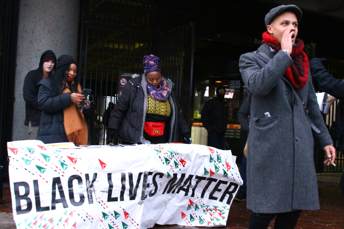 """The Black Lives Matter DC Direct Action POD joined Save Our System, The Future Is Feminist, and other groups for """"Swipes On Us,"""" stand Jan. 8 outside the Anacostia Metro Station in southeast D.C., where they spoke out against Metro policies that are seen to disproportionately affect low-income residents and communities demographically similar to Anacostia. Organizers distributed free, preloaded SmarTrip cards to residents, in part to raise awareness and to help offset the potential impact of Metro's new policy against negative SmarTrip balances. (E Watson/EDI Photo)"""