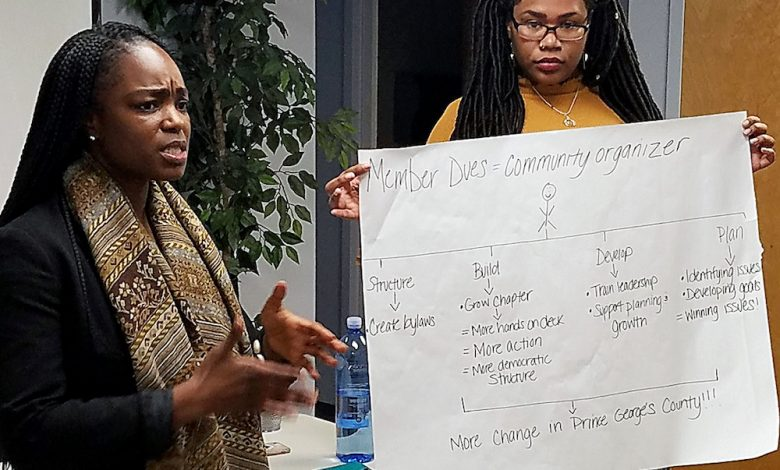 Seanniece Bamiro (left) explains how membership in a Prince George's County co-op with Progressive Maryland would help to hire a full-time community organizer. Alexiss Kurtz holds the paper that outlines some of the responsibilities and goals. (William J. Ford/The Washington Informer)