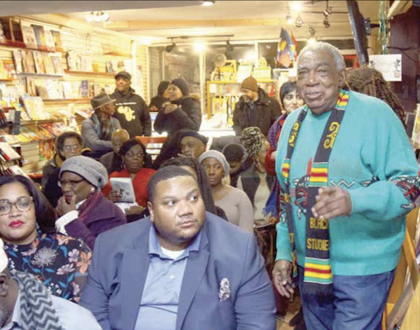 """A. Peter Bailey (far right) moves to address the audience during the screening of """"Malcolm X: An Overwhelming Influence on America's Black Power Movement"""" at Sankofa Video Books & Cafe in northwest D.C. on Jan. 3. (E Watson/EDI Photo)"""