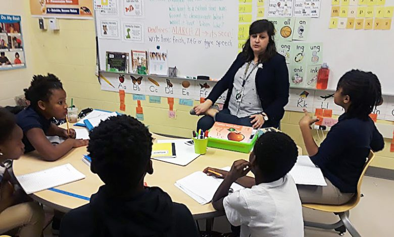 Sarah Baraba, a teacher adviser for Ketcham Elementary School's Anthology Club, coaches student members during one of their Wednesday meetings. (Dorothy Rowley/The Washington Informer)