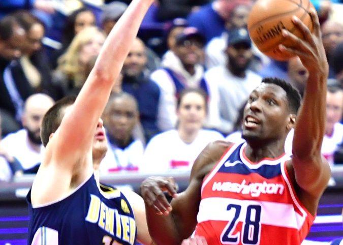 Washington Wizards center Ian Mahinmi shoots over Denver Nuggets center Nikola Jokic during the Nuggets' 108-100 win at Capital One Arena in D.C. on March 23. (John De Freitas/The Washington Informer)