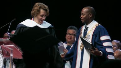Author Paula J. Giddings (left), speaker for Howard University's 2018 Charter Day Convocation, is greeted by Howard President Wayne A.I. Frederick during the university's 2018 Charter Day Convocation at Cramton Auditorium on Howard's northwest D.C. campus on March 2. (Shevry Lassiter/The Washington Informer)