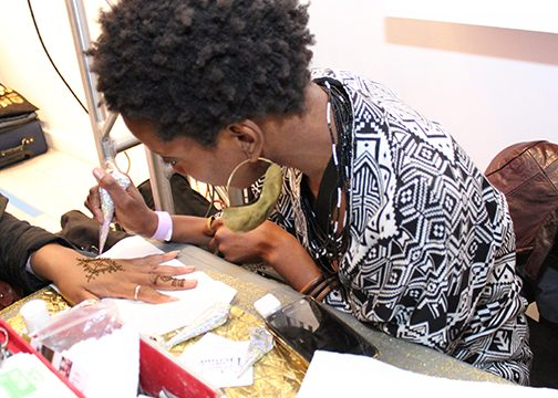 An artist paints the hand of a guest during the Black Love Fest. (Brigette White/The Washington Informer)