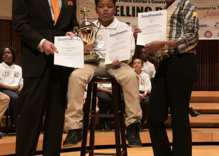 David Zahren, pronouncer and moderator of the 2018 Prince George's County Spelling Bee and Bee coordinator Chauka Reid and winner Kayden Wilkins display their Southwest Airlines certificates for travel. (Shevry Lassiter/The Washington Informer)