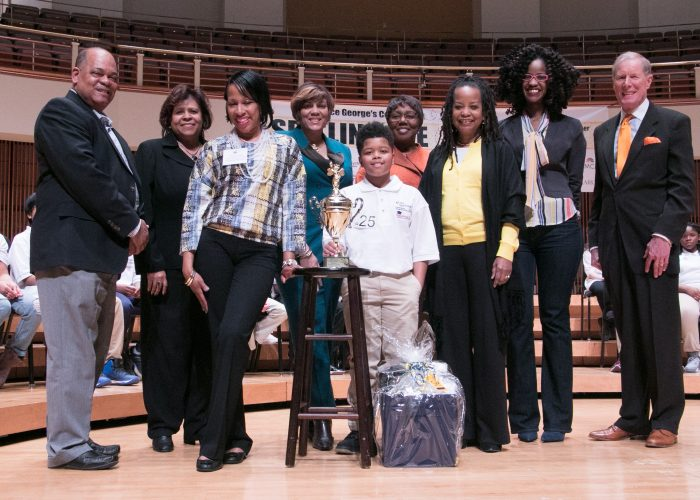 The 2018 Prince George's County Spelling Bee winner, Kayden Wilkins is joined on stage by Spelling Bee sponsors at the Clarice Smith Performing Arts Center on the campus of Maryland University in College Park on Friday, March 16. (Shevry Lassiter/The Washington Informer)