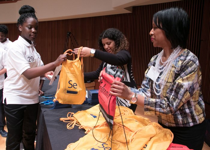 Prince George's County 2018 Spelling Bee Coordinator Chauka Reid and a volunteer hand out bags prepared by the Bee sponsors to spellers. (Shevry Lassiter/The Washington Informer)