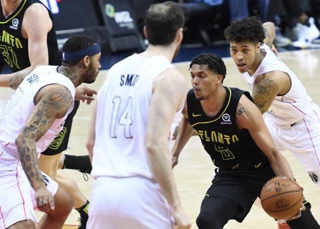 Atlanta Hawks guard Damion Lee drives between Washington Wizards defenders during the Hawks' 103-97 win at Capital One Arena in D.C. on April 6. (John De Freitas/The Washington Informer)