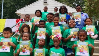 D.C. People's Counsel Sandra Mattavous-Frye and Community Outreach Specialist Denise Blackson pose with children attending an OPC energy efficiency workshop at Upshur Recreation Center in northwest D.C. as part of OPC's partnership with the D.C. Department of Parks and Recreation.