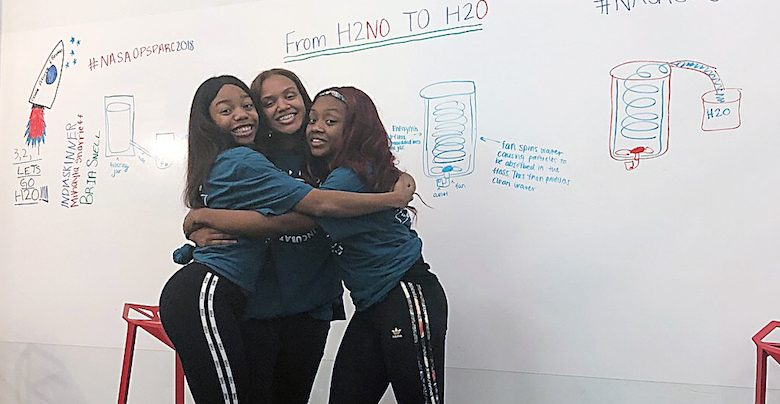 Banneker High School students Bria Snell, India Skinner and Mikayla Sharrieff, finalists in a national NASA competition, hug each other. (Courtesy of In3)