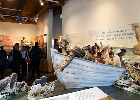 Harriet Tubman reaches into a river to rescue runaways escaping slavery on one of her journeys to free for her people. (Roy Lewis/The Washington Informer)