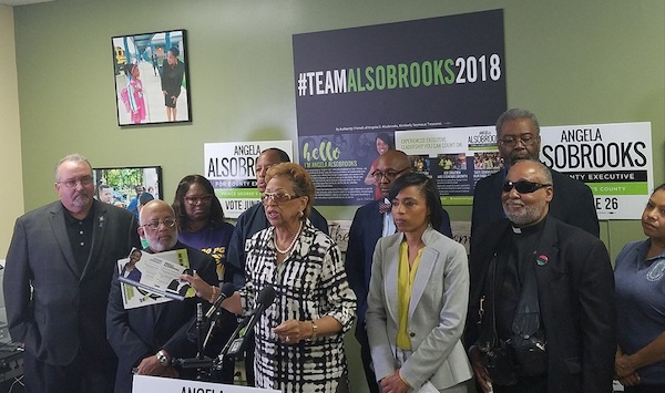 Former Maryland state Sen. Gloria Lawlah holds campaign literature from a super PAC that accuses Prince George's County State's Attorney and county executive hopeful Angela Alsobrooks (in gray and yellow) of fostering a pay-to-play culture with developers during a May 16 press conference at Alsobrooks' campaign headquarters in Largo. (William J. Ford/The Washington Informer)