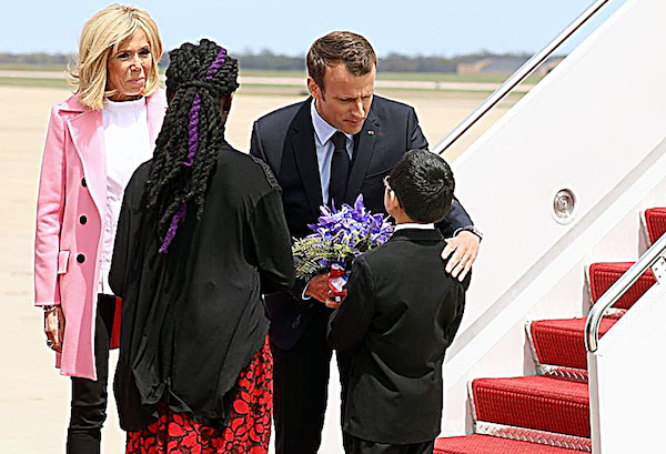 French President Emmanuel Macron and his wife Brigitte greet fourth-graders Owen Sze (right) and Marissa Tyler after exiting a plane at Joint Base Andrews. The two students were among the first people to greet Macron and his wife upon their visit to the U.S. in April. (Courtesy of the Embassy of France in the U.S.)