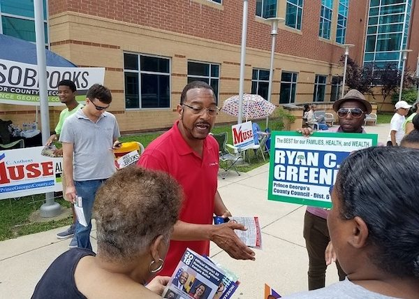 C. Anthony Muse (left), who is running for Prince George's County executive, chats with voters June 26 outside Dr. Henry E. Wise Jr. High School in Upper Marlboro during the Maryland primary election. (William J. Ford/The Washington Informer)
