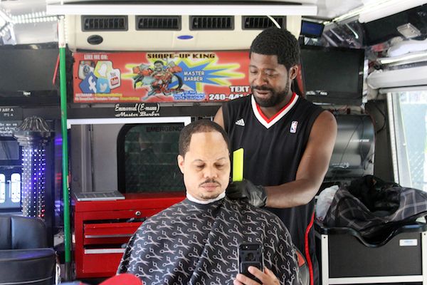 "Emmanuel ""E-Man"" Azoro, also known as ""The Shapeup King,"" tends to a customer inside his mobile barbershop during the second annual Man Cave at Emery Heights Father's Day Celebration on June 16. (Courtesy of Man Cave at Emery Heights)"